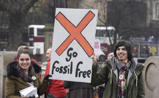 Two protestors in Edinburgh hold up 'go fossil free' banner.