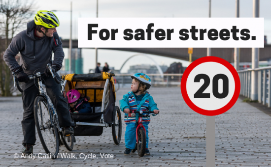 """Man and small child on bicycles.  Text saying """"For Safer Streets"""" and 20mph speed limits"""